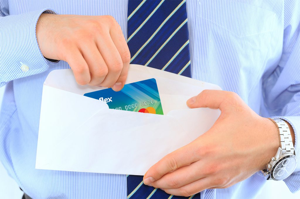 Man opens envelope with a Reflex Mastercard inside